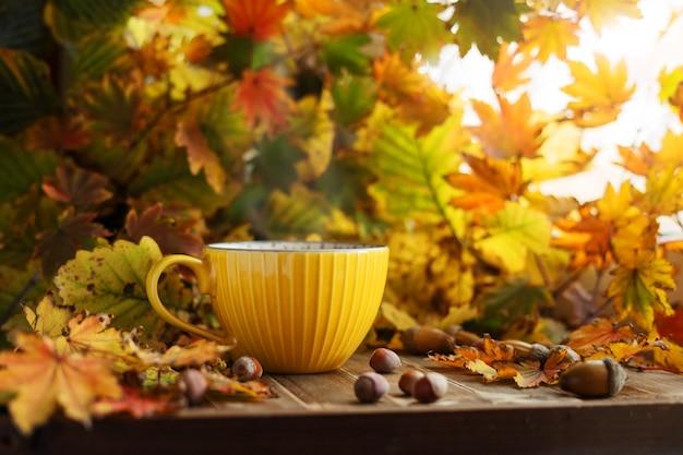 Żółta filiżanka herbaty w liściach jesienią z żołędziami i orzechami. jesienny klimat.