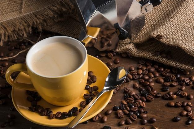 Żółta filiżanka w pobliżu rozproszonych ziaren kawy i wory