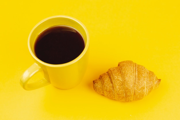 Żółta filiżanka z kawą i croissant na żółtym tle