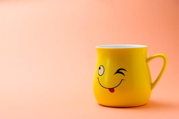 Żółta filiżanka z mrugającym uśmiechem na kolorowym