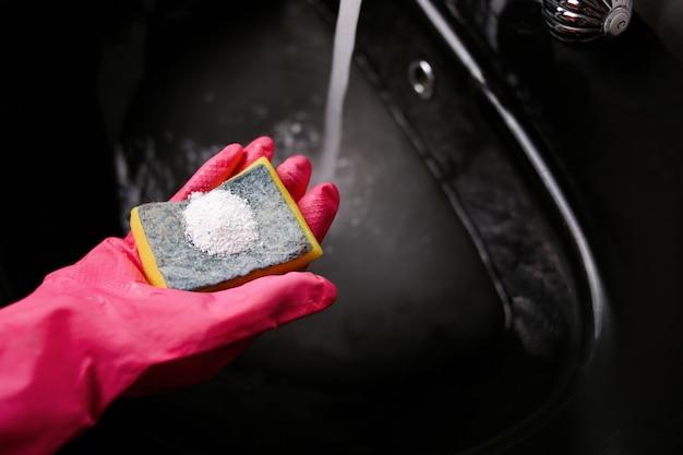 Żółta gąbka do czyszczenia w różowych rękawiczkach z proszkiem do dezynfekcji na tle czarnego zlewu z wodą. wysokiej jakości zdjęcie