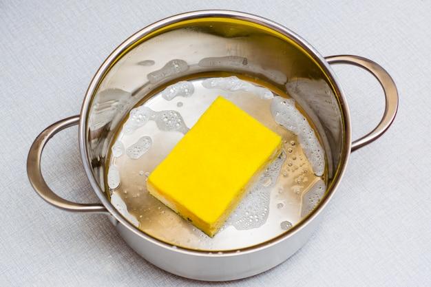 Żółta gąbka do mycia naczyń leży na dnie mydlanej patelni na stole.
