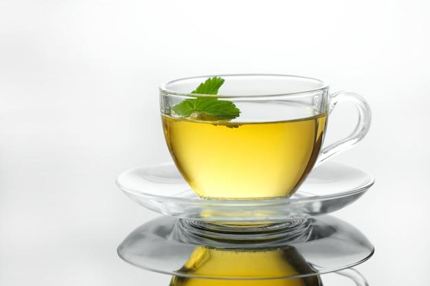 Żółta herbata ziołowa w filiżance z liśćmi zbliżenie świeżo parzonej gorącej herbaty na białym tle