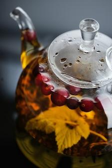 Żółta herbata ziołowa w szklanym czajniczku i filiżance z liśćmi i jagodami zbliżenie świeżo parzona gorąca herbata