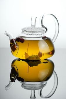 Żółta herbata ziołowa w szklanym czajniczku z liśćmi i jagodami świeżo parzonej gorącej herbaty ze szklanym tłem refleksyjnym reflection