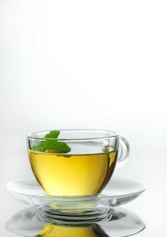 Żółta herbata ziołowa w szklanym kubku z ziołowymi liśćmi zbliżenie świeżo parzonej gorącej herbaty na białym tle