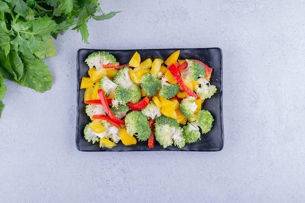 Żółta i czerwona sałatka z papryki i brokułów na talerzu obok stosu zieleni na marmurowym tle. zdjęcie wysokiej jakości