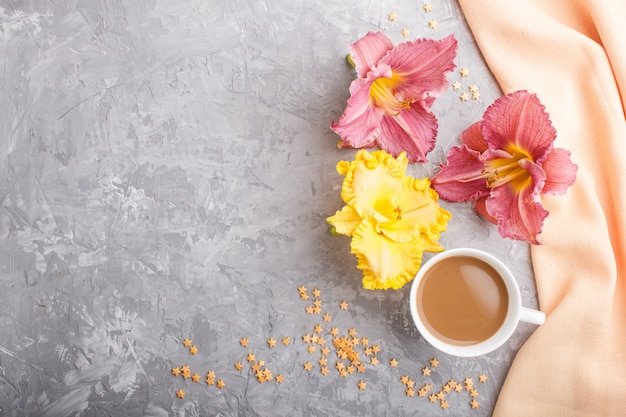 Żółta i fioletowa filiżanka kawy z liliami dziennymi, z pomarańczowym materiałem. widok z góry, lato.