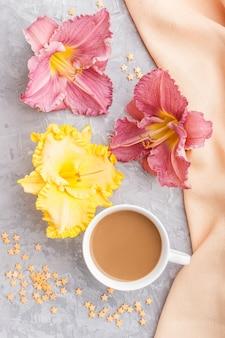 Żółta i fioletowa filiżanka kawy z liliami dziennymi, z pomarańczowym materiałem. widok z góry.