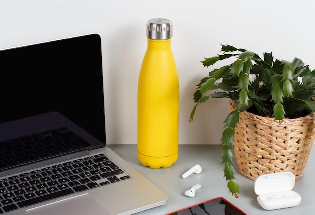 Żółta izolowana butelka na szarym biurku otoczona nowoczesnymi gadżetami i rośliną w wazonie z bliska