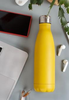Żółta izolowana butelka na szarym biurku otoczona nowoczesnymi gadżetami i rośliną w widoku z góry wazonu