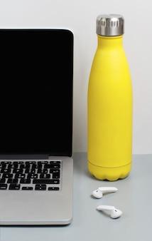 Żółta izolowana butelka na szarym biurku w pobliżu laptopa z bliska