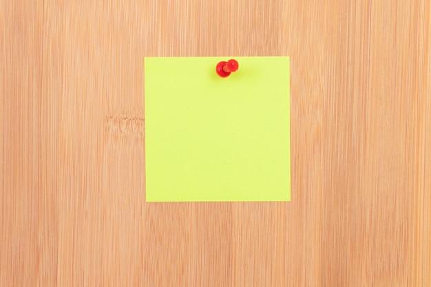 Żółta karteczka przypięta do drewnianej tablicy ogłoszeń