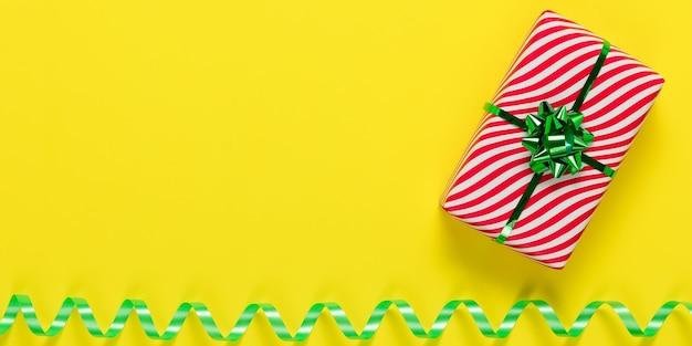 Żółta kartka i białe pudełko w czerwone paski z zieloną kokardką i serpentynową wstążką.