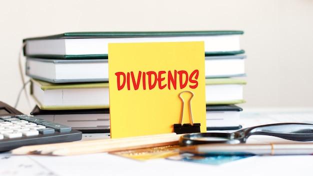 Żółta kartka papieru z tekstem dywidend stoi na klipsie do dokumentów na biurku na tle ułożonych książek, kalkulator, karty kredytowe. koncepcja biznesowa i finansowa. selektywne skupienie.