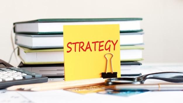 Żółta kartka papieru ze strategią tekstową stoi na spinaczu do dokumentów na biurku przed ułożonymi książkami, kalkulatorem, kartami kredytowymi. koncepcja biznesowa i finansowa. selektywna ostrość.
