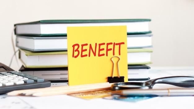 Żółta kartka z tekstem benefit stoi na spinaczu na papiery na biurku, obok książek, kalkulatorów, kart kredytowych. koncepcja biznesowa i finansowa. selektywna ostrość.