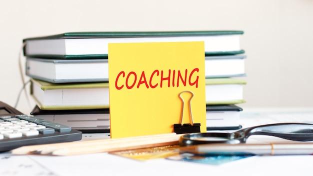 Żółta kartka z tekstem coachingowym stoi na spinaczu na papiery na biurku, na tle ułożonych książek, kalkulatora, kart kredytowych. koncepcja biznesowa i finansowa. selektywna ostrość.