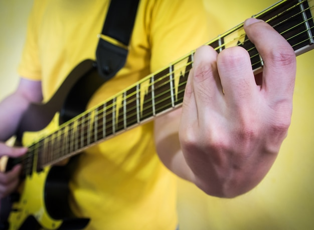 Żółta koncepcja: człowiek gra na gitarze