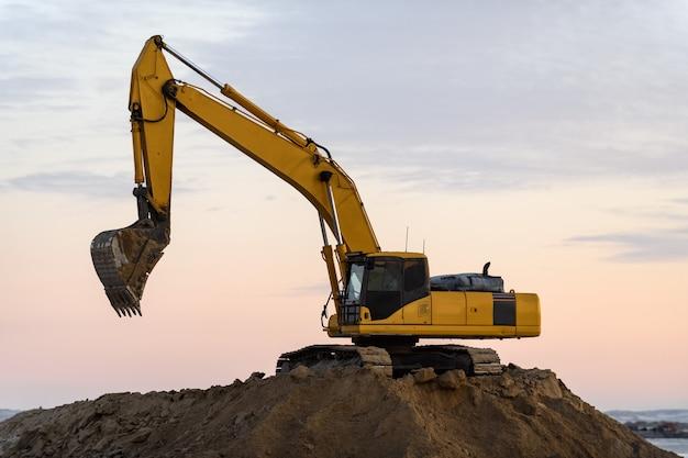 Żółta koparka pracuje na budowie. budowa drogi.