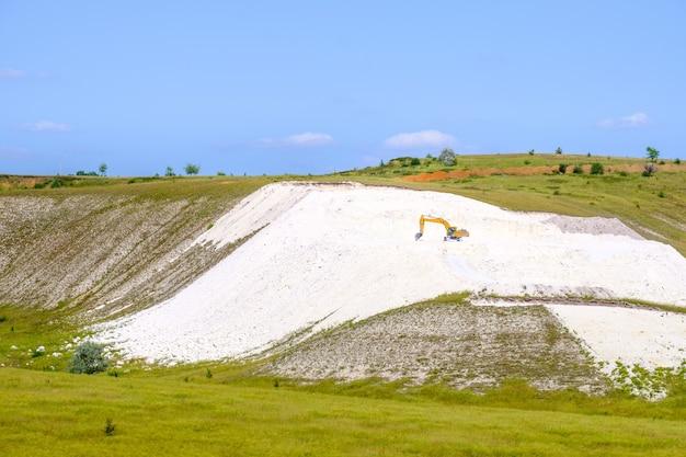 Żółta koparka pracuje w kamieniołomie kredy.