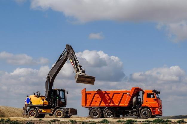 Żółta koparko-ładowarka ładuje ziemię do ciężarówki podczas budowy drogi