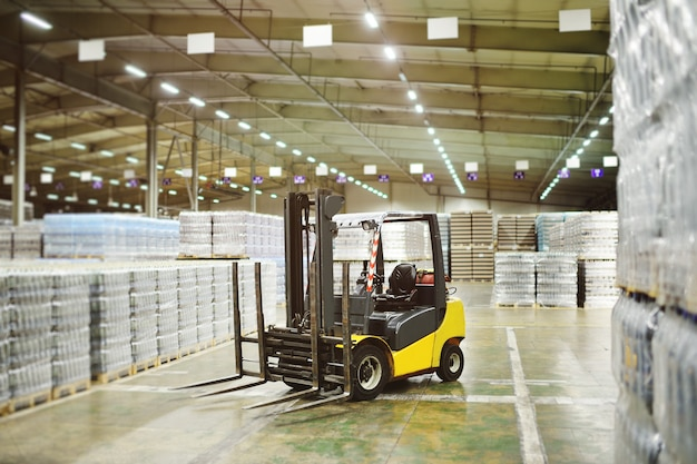 Żółta ładowarka na tle ogromnego przemysłowego magazynu żywności z plastikowymi butelkami pet z piwem, wodą, napojami.
