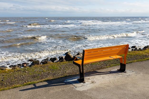 Żółta ławka na chodniku nad morzem