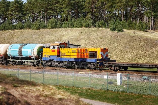 Żółta lokomotywa towarowa z czołgami wśród wzgórz i lasów latem
