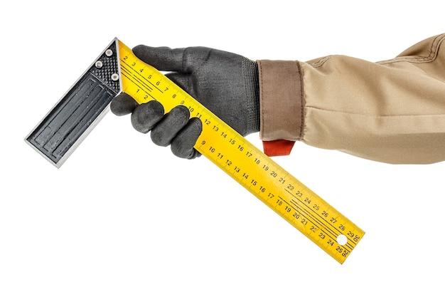Żółta metalowa linijka kwadratowa w ręku stolarza w czarnej rękawicy ochronnej i brązowym mundurze na białym tle