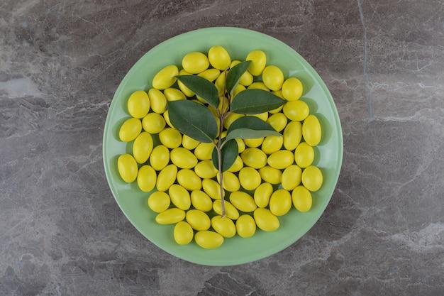 Żółta miętowa guma na talerzu, na marmurowej powierzchni