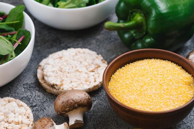 Żółta miska z polentą; dmuchany placek ryżowy; grzyb i papryka