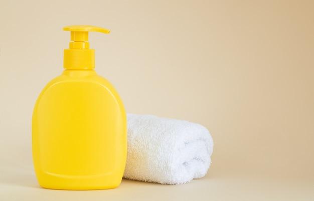 Żółta niemarkowa butelka z dozownikiem obok białego ręcznika na beżowym tle