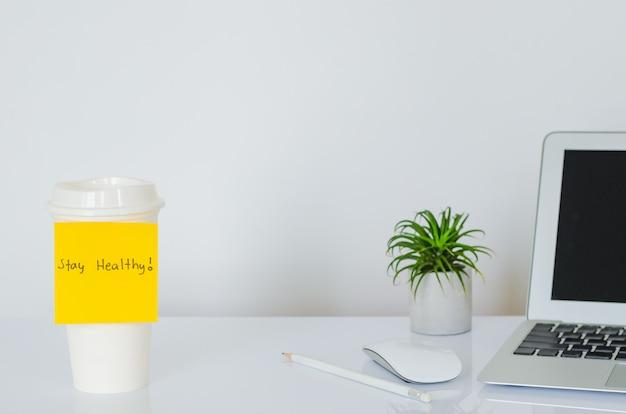 Żółta nuta ze słowem stay healthy przyklej do kubka z kawą, aby kibicować sytuacji wirusa covid-19 lub wirusa korony na całym świecie.