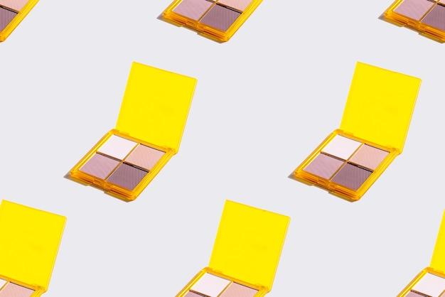 Żółta paleta cieni do powiek na szarej ścianie, kosmetyk do cieni do powiek. wzór. modny kolor 2021
