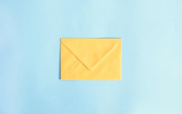 Żółta papierowa koperta na jasnoniebieskim tle. świąteczny szablon. projekt karty z pozdrowieniami. widok z góry.