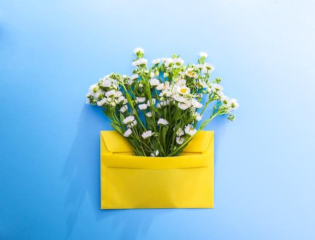 Żółta papierowa koperta z małymi ogrodowymi kwiatami rumianku białego na jasnoniebieskim tle. świąteczny kwiatowy szablon. projekt karty z pozdrowieniami. widok z góry.