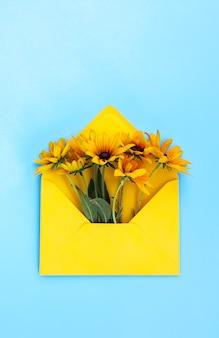 Żółta papierowa koperta z ogrodowymi kwiatami rudbeckia na jasnoniebieskim tle. świąteczny kwiatowy szablon. projekt karty z pozdrowieniami. widok z góry. zabytkowy styl. czarnooka roślina susan.
