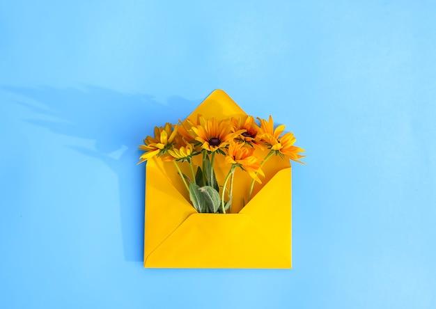 Żółta papierowa koperta z ogrodowymi kwiatami rudbeckia na jasnoniebieskim tle. świąteczny kwiatowy szablon. projekt karty z pozdrowieniami. widok z góry. zabytkowy styl. czarnookie rośliny susan.