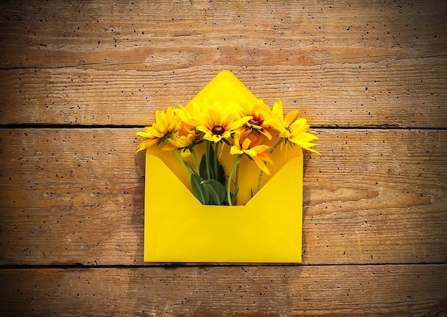 Żółta papierowa koperta z rudbeckia lub czarnooka susan kwiaty ogrodowe na tle starych desek. styl rustykalny. świąteczny kwiatowy szablon. projekt karty z pozdrowieniami. widok z góry.
