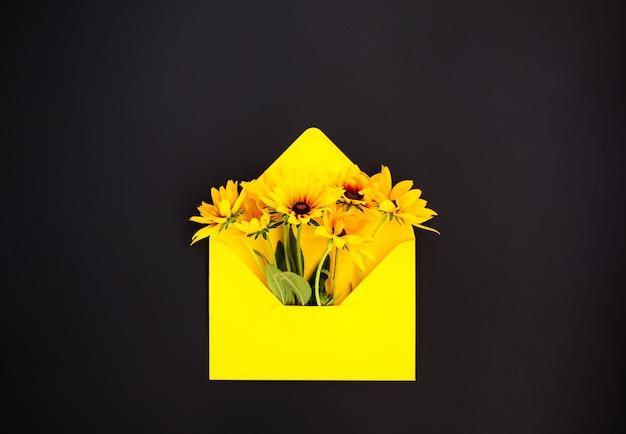 Żółta papierowa koperta z rudbeckia lub czarnookimi kwiatami ogrodowymi susan na ciemnym tle. świąteczny kwiatowy szablon. projekt karty z pozdrowieniami. widok z góry.