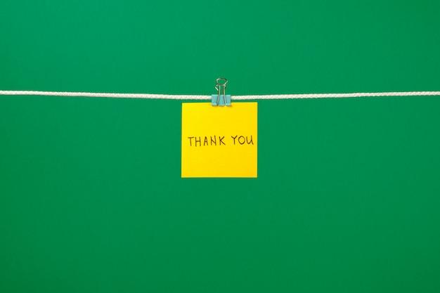 Żółta papierowa notatka na sznurku z tekstem dziękuję