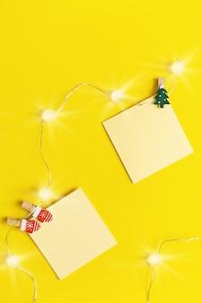 Żółta papierowa notatka zauważa choinki. puste lepkie kwadratowe przypomnienie do pisania pomysłów, rzeczy do zrobienia.