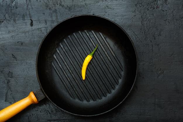 Żółta papryka chili na patelni grillowej na czarnym tle kamienia. widok z góry, płaski, minimalistyczny