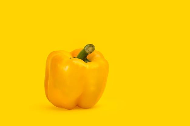Żółta papryka na białym tle na żółtym tle z miejsca kopiowania po prawej stronie