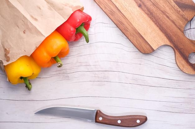 Żółta papryka pomarańczowa i czerwona z deską do krojenia na stole