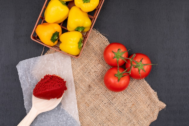 Żółta papryka w koszu obok kiści pomidorów i koncentratu pomidorowego w łyżce na czarno