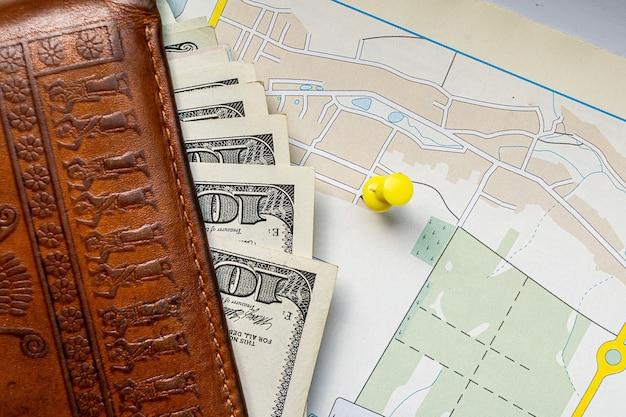 Żółta pinezka nad mapą z banknotami dolarowymi wystającymi z portfela