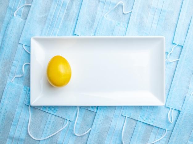 Żółta pisanka na białym talerzu ceramicznym na tle niebieskich masek medycznych