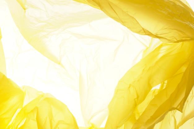 Żółta plastikowa torba tekstura. żółte tło z tworzywa sztucznego.